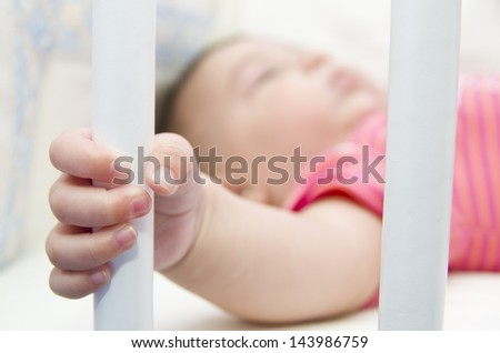 Captive baby, holding a crib bar. Security and children. Focus in the hand. - stock photo
