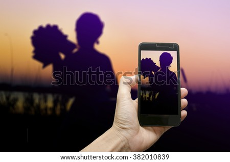 capture camera smartphone,silhouette beautiful women with photography pre wedding outdoor the sunset - stock photo