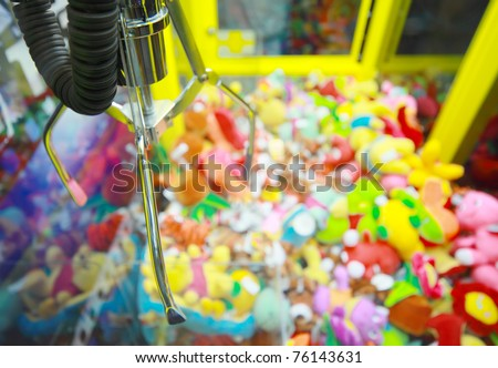 Capture device for soft toys on background of heap of colorful soft toys in arcade machine - stock photo