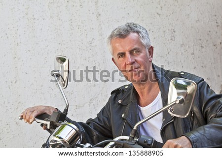 Capture of a Caucasian motor biker in trendy casual attire and relaxed expression looking into lens sat on a red cruiser. Generic shot location was Bombay India - stock photo