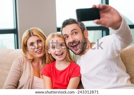 Capturing a bright moment together. Happy family of three bonding to each other and smiling while father photographing them with smart phone  - stock photo