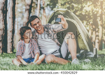Capturing great moments. Cheerful father and son making selfie while sitting near the tent in the forest - stock photo