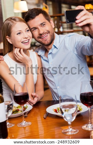 Capturing romantic moments. Beautiful young loving couple making selfie and smiling while sitting at the restaurant together  - stock photo