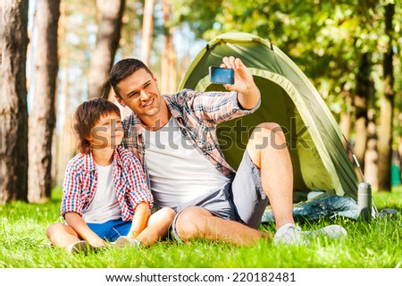 Capturing the bright moments. Cheerful father and son sitting near the tent while camping in the forest   - stock photo