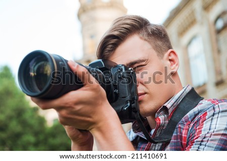 Capturing the moment. Handsome young man taking a photograph with his digital camera while standing outdoors - stock photo