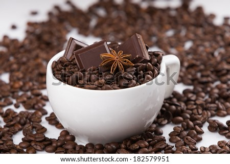 Capuccino cup filled with coffee beans, sweet chocolates and aniy star - stock photo