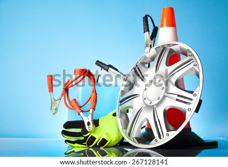 Car accessories - car hubcap with jump start cables in front of traffic cone with washer fluid and a pair of green gloves on blue background - stock photo