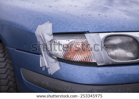 Car accident, insurance concept with adhesive tape on lights - stock photo