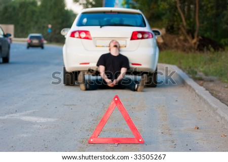 Car accident on a road. Focus is on the red triangle sign - stock photo