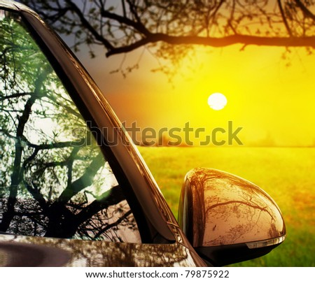 Car against sunset in the background - stock photo