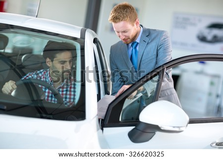 Car agent and customer in car showroom,  together watching the performance of vehicle - stock photo