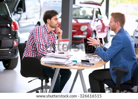 car agent talking with male customer at car dealership saloon - stock photo