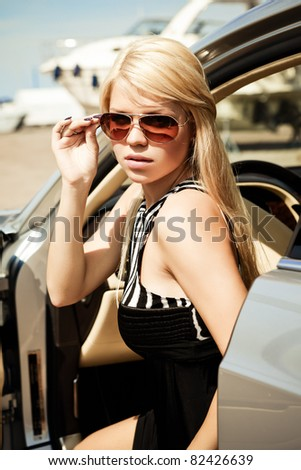 Car and babeYoung sexy blond girl sitting in a luxury car - stock photo