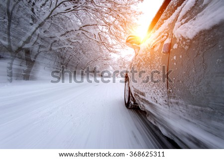 Car and falling snow in winter on forest road with much snow.(Motion blur) - stock photo