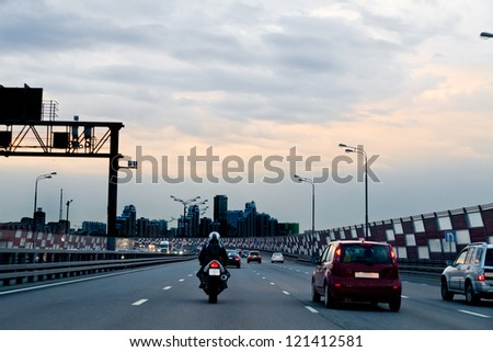 Car and motorcycle on the highway-evening. The urban landscape. - stock photo