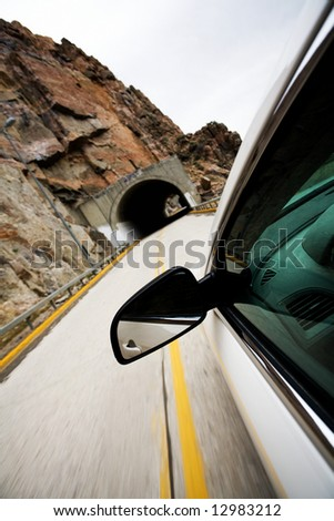 car approaching tunnel through the mountains. Focus on mirror, motion blur on road. - stock photo