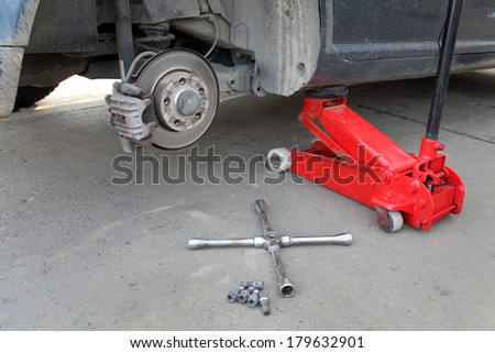 Car at hydraulic jack, disc brakes, screws and  lug wrench tool - stock photo