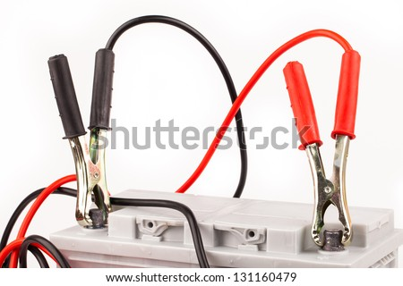 Car battery and jumper cables isolated on white - stock photo