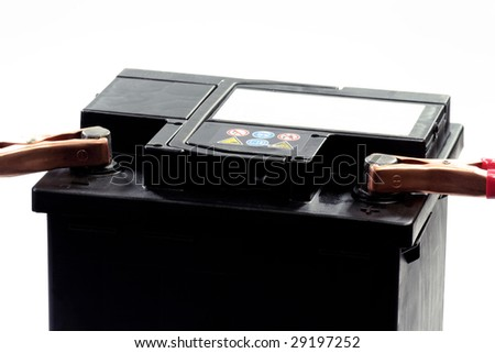 Car battery with electrical leads clipped on to the terminals - isolated over white - stock photo