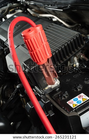 car battery with jumper cable in engine room - stock photo