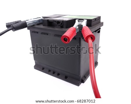 Car battery with two jumper cables clipped to the terminals shot over white - stock photo