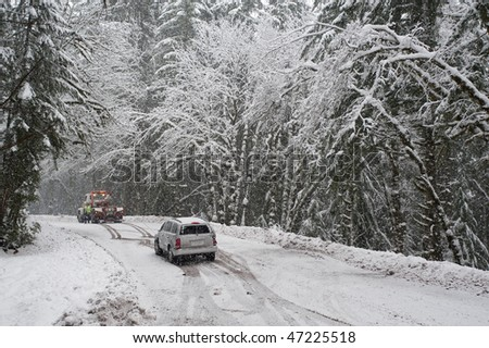 Car being towed after accident in snow storm - stock photo