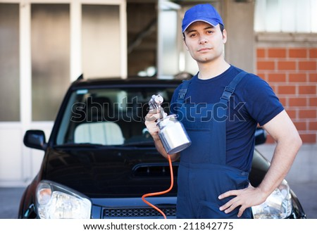 Car body repairer holding a spray gun - stock photo