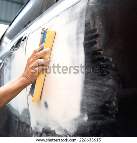 Car body work auto repair paint after the accident ust sand paper hand. - stock photo