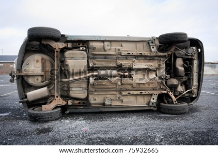car bottom turned on the side after road collision - stock photo