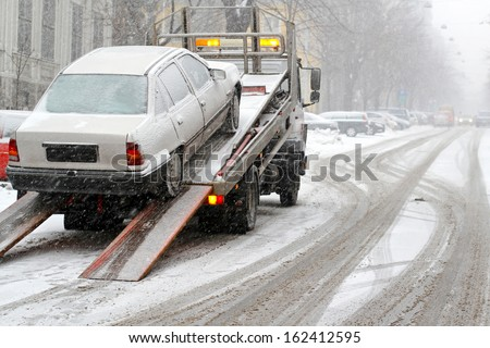 Car break down and towing at snow street  - stock photo