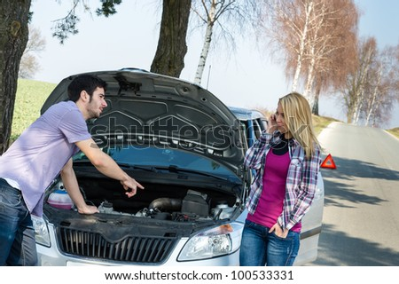 Car breakdown couple calling for road assistance man point engine - stock photo