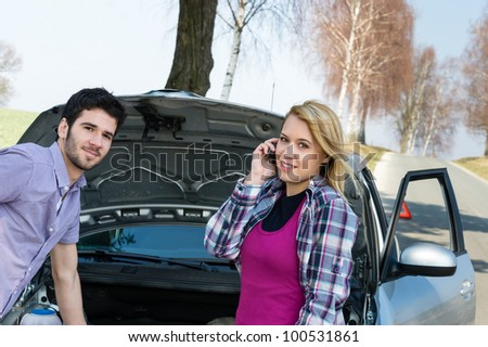 Car breakdown couple calling for road assistance repair motor defect - stock photo