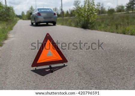 car broken down and a red triangle to warn other road users - stock photo