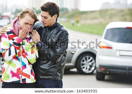 Car collision. Driver man and upset woman in front of damaged automobile cars after crash accident in city - stock photo