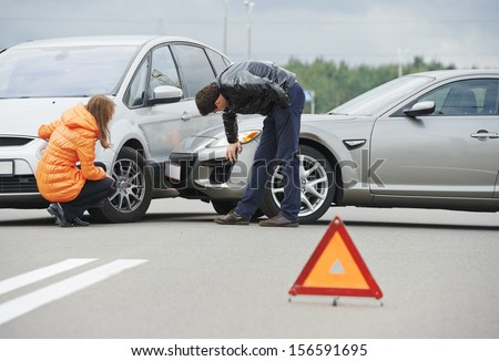 Car collision. driver man and woman examining damaged automobile cars after crash accident in city - stock photo