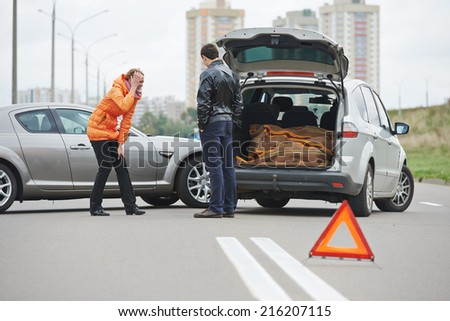 Car collision. upset driver woman and man debating near damaged automobile cars after crash accident in city - stock photo
