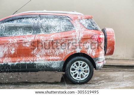 car covered in foam at the carwash - stock photo