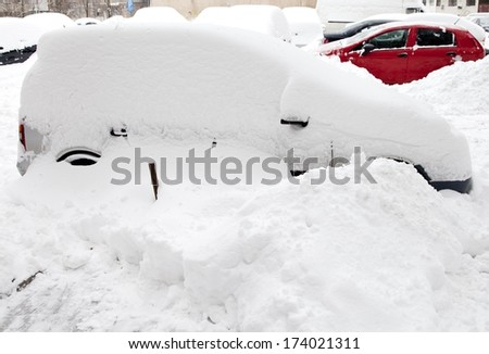 Car covered with snow in the parking after a snow storm - stock photo