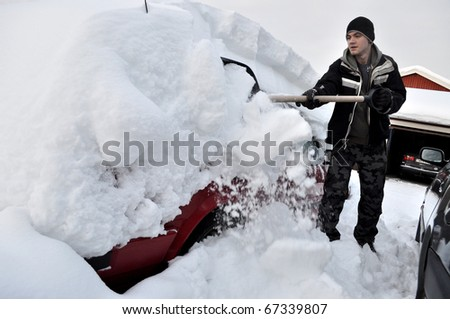 car covered with snow in winter time - stock photo