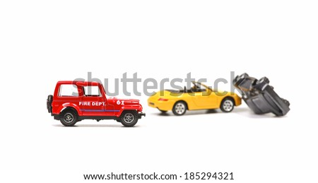 Car crash between a yellow sportscar and a black sedan with fire dept car. Simulation with model cars - stock photo