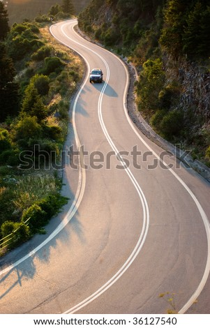 car crosses country road winding in twilight