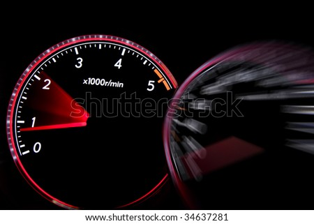 Car dashboard gauges illuminated at night, tachometer, speedometer
