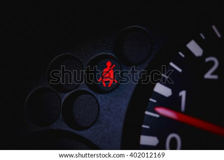 Car Dashboard showing the seat belt warning light