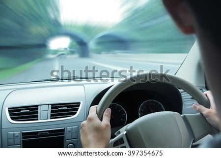Car dashboard with a man holding the steering wheel, driving fast into a tunnel on the road - stock photo