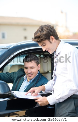 Car dealer and happy smiling man signing a contract. Concept for car rental  - stock photo