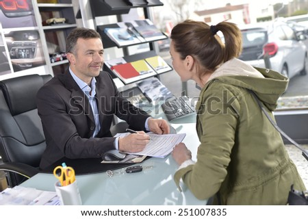 Car dealer editing purchase agreement to buyer - stock photo