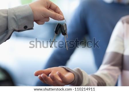 Car dealer giving keys to a customer in a car shop - stock photo