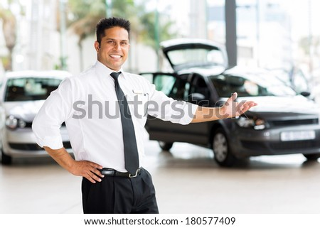 car dealer presenting new vehicle in showroom - stock photo