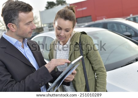 Car dealer showing car specifications to client on tablet - stock photo