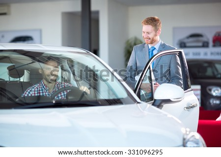 car dealer showing new car to customer - stock photo